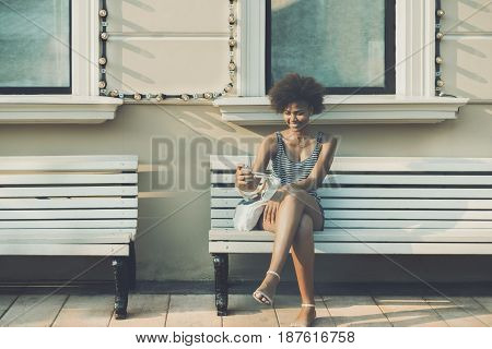 Cheerful curly Brazilian girl making selfie while sitting on bench during summer day withs copy space for text charming laughing teenage female with smart phone surfing her social network accounts