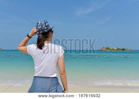 Back view of blissful woman at tropical beach enjoying relax freedom and vacation. Smile Freedom and happiness woman on beach.