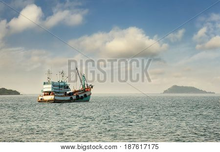 Wooden fishing boat on the beach/Fishing boat on the beach blue sky background in Thailand/The fishing boat at sandy beach/Tropical beach Andaman sea Thailand wooden fishing boat on sea in morning
