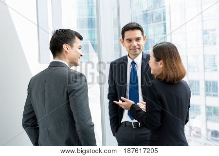 Group of business people talking in building hallway during break at work
