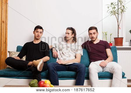 Cool looking friends hanging out together in nice confortable room. Male friendship