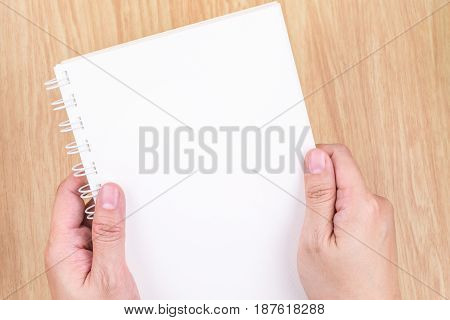 Close Up Two Hand Holding Empty White Open Book Above Wood Desk ,mock Up Template For Adding Your Co