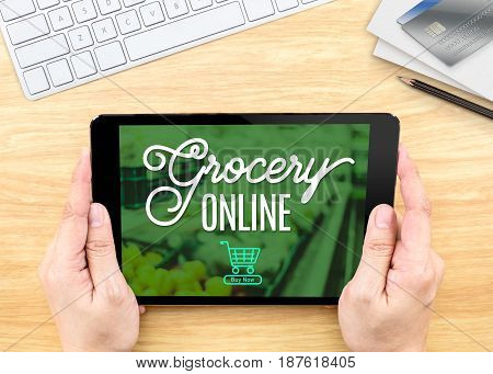 Hand Holding Tablet With Grocery Online Word On Wood Table ,shopping Online Concept.