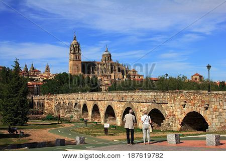 Salamanca, Spain - May 7, 2014. Elderly pair enjoys the beautiful view on ascent romanian bridge and  Cathedral of Salamanca