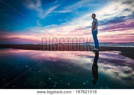 Amazing sea sunset with reflection. Solitary man. A colorful sunset sea, man standing observing the beauty of nature. The sky and the man are reflected in a pool of water in front of the sea.