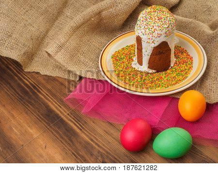 Easter cake, ceramic bowl with colorful sweet powder and easter colored egg. Russian and Ukrainian, orthodox slavic traditional Easter kulich on rural background. Old wood, red mesh paper and burlap.