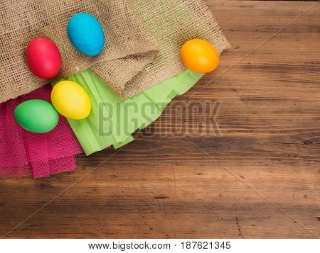 Easter eggs on old brown wood background with borlap and green paper. Top view, horizontal. Mock up for your poster. Russian and Ukrainian, orthodox, slavic traditional Easter, rural background.