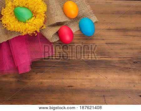 Colored chicken eggs on background of bright yellow straw, burlap and old wooden table. The view from the top. The view from the top. Creative background for greeting cards, menu or advertising