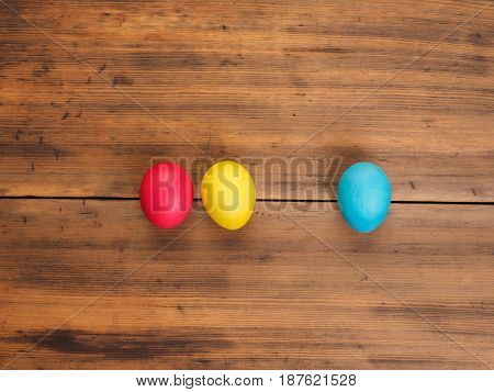 Easter eggs on old brown wood background. Top view, horizontal. Mock up for your greetings card, poster or other design. Russian and Ukrainian, orthodox, slavic traditional Easter, rural background.