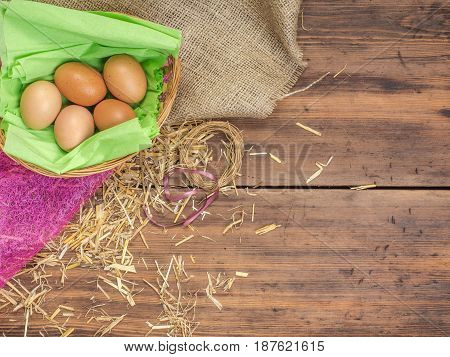 Rural eco background with brown chicken eggs, a piece of burlap and straw on the background of old wooden planks. The view from the top. Creative background for Easter cards or menu