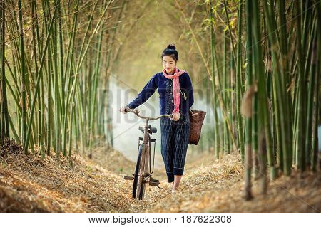 Asian woman walk alone on an ancient bicycle.