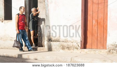 Trinidad, Cuba - July 2, 2012; Man standing in doorway of Spanish style home in Cuba points way to another in red tank top standing on footpath in Cuban town.