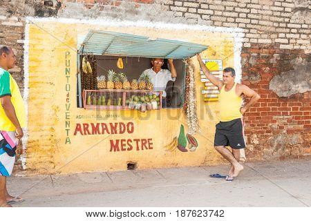 Trinidad, Cuba -July 2, 2012; Hole in wall fruit shop with Spanish sign vendor behind fruit display man standing casually in Trinidad de Cuba.