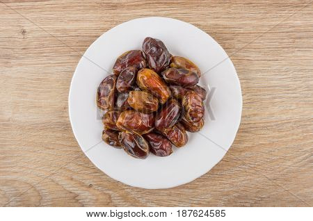 White Glass With Dried Dates On Wooden Table