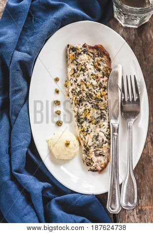 Fish Mackerel Baked With Herbs, Mashed Potatoes, Pesto Sauce Served On A White Plate On A Wooden Ant