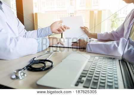 Two Doctors Discussing Patient Notes In An Office Pointing To A Clipboard With Paperwork As They Mak