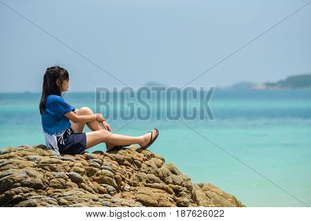 Lonely girl sitting at the beach with sea. Thoughtful and loving. Young girl sitting on the beach relaxing. In the background the waves of the Mediterranean Sea