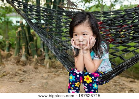 Unhappy Girl Sitting Alone In Hammock.. Outdoor On Summer Day.