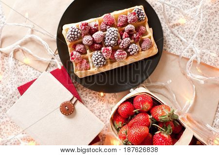 Waffle with raspberry and blackberry books and fresh strawberry on table closeup. Top view. Good morning.