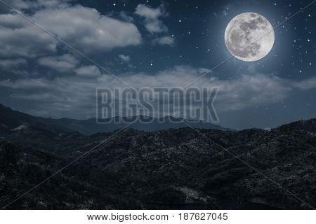 Landscape of night sky with many stars and cloudy above mountain peak. Beautiful bright super moon over tranquil nature on dark tone. The moon taken with my own camera.