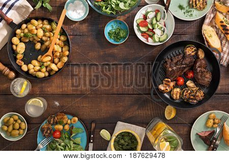 Frame of grilled steak grilled vegetables potatoes salad different snacks and homemade lemonade top view. Concept dinner table