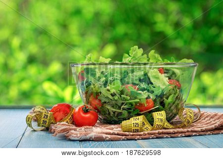 Large bowl of salad with measuring tape on blue wooden table. Weight loss or diet food concept