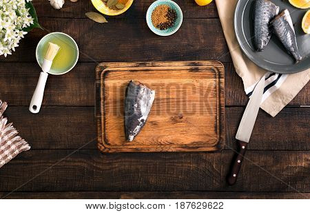 Fresh raw fish with lemon and spices for cooking healthy food on wooden kitchen board top view. Healthy food and diet concept