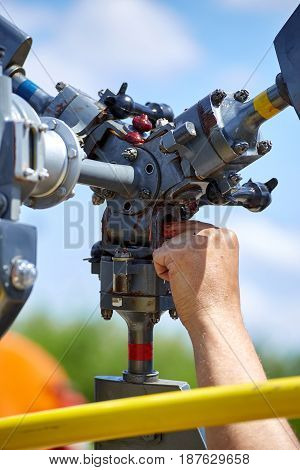 Service and lubrication of a three-bladed helicopter screw on a sunny day.