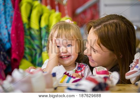 Mother and her little daughter buy a shoes in children store, telephoto