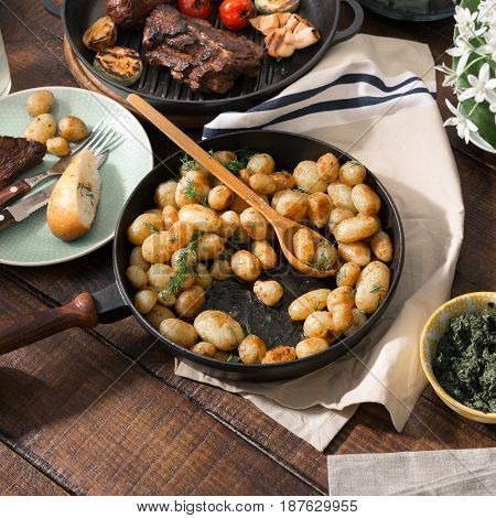 Fried young potatoes in a cast-iron frying pan on wooden table with grilled meat. Concept dinner table