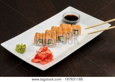 Philadelphia maki sushi rolls with salmon cheese cream and cucumber on white plate