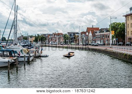 Alkmaar Netherlands - August 5 2016: Canal of Alkmaar with nautical vessels and cityscape a cloudy day. Alkmaar is well known for its traditional cheese market. For tourists it is a popular cultural destination