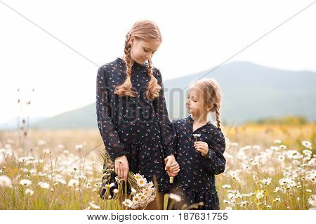 Smiling teen girl 12-14 year old with kid girl 4-5 year old walking in chamomile meadow. Two sisters in similar dresses posing outdoors. Childhood. Summer time.