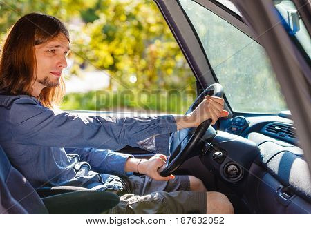Fresh driver traveling concept. Young man wearing jeans shirt having long hair driving car carefully on sunny day