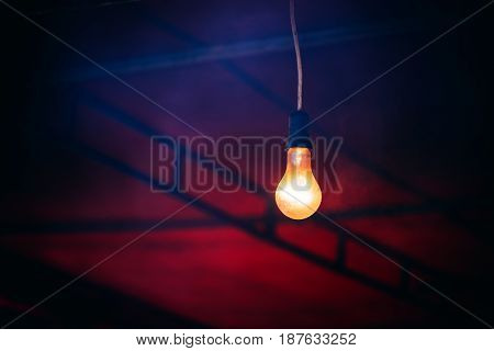 Old light bulb glowing in the dark