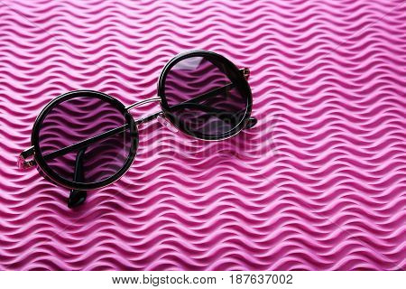 Black sunglasses on the pink background, close up