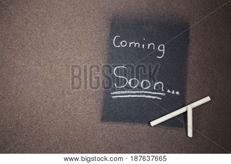 a coming soon sign made chalk on a blackboard