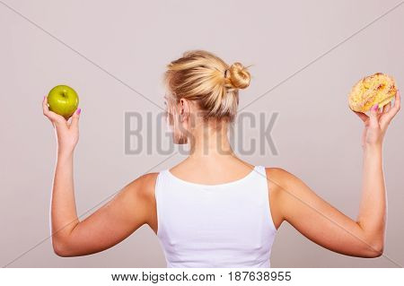 Woman back view holds in hand cake sweet bun and apple fruit choosing trying to resist temptation make the right dietary choice. Weight loss diet dilemma concept.