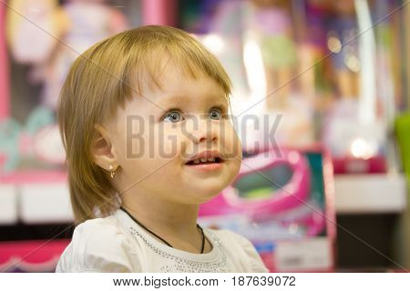 Portrait of the little girl among toys in children store, telephoto