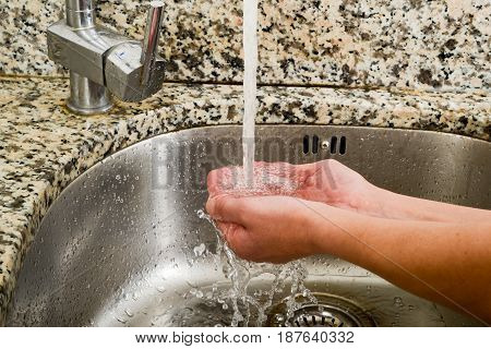 Woman Takeing Water With Her Hands From A Tap