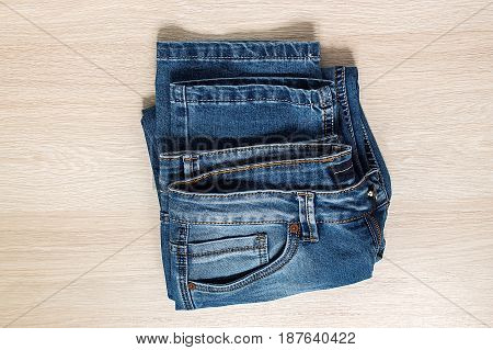 New blue jeans on wooden background top view