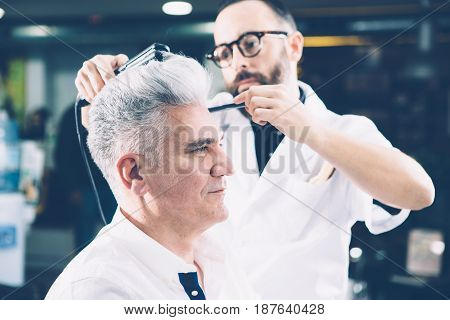 Side view of stylist working with hairdo of mature man in barbershop. Horizontal indoors shot.