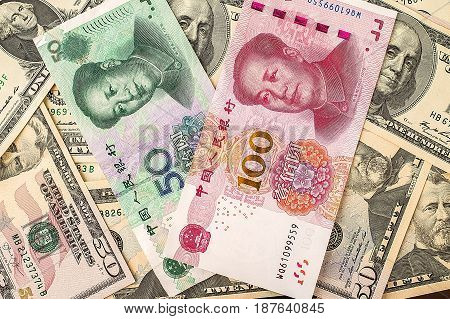 Chinese yuan bank note on USA dollars background, Chinese and USA economy finance trade business, money closeup