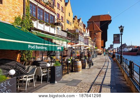 GDANSK POLAND - MAY 19 2017: Street scene with peoples walk on riverside with the characteristic medieval Crane in Gdansk. Old Town in Gdansk is a tourist attraction for visitors.