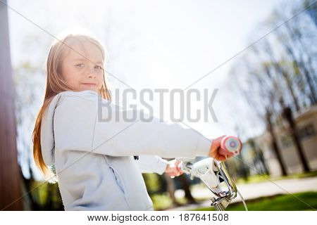 Photo of girl with bicycle in park during day