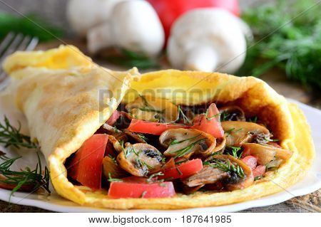 Mushrooms, tomatoes omelette breakfast. Omelette stuffed with mushrooms, tomatoes and dill on a plate and old wooden background. Easy eggs breakfast for whole family. Rustic style. Closeup