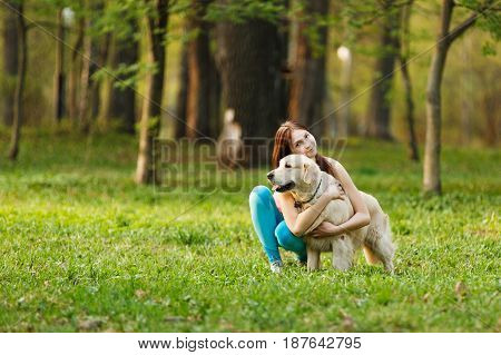 Owner with favorite labrador in park on lawn