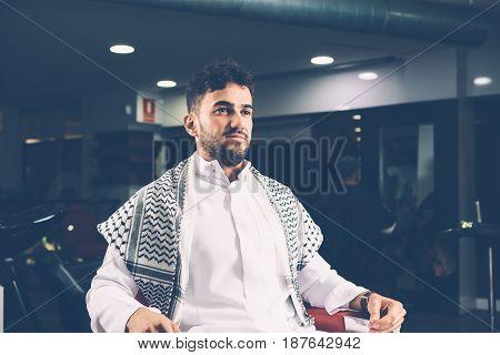 Handsome man sitting in armchair in barber shop. Horizontal indoors shot.