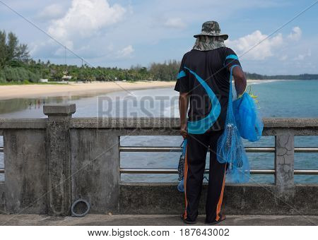 Fisherman Standing On Concrete Bridge. Him Holding Fishing Nets And Looking Place For Fishing. Front