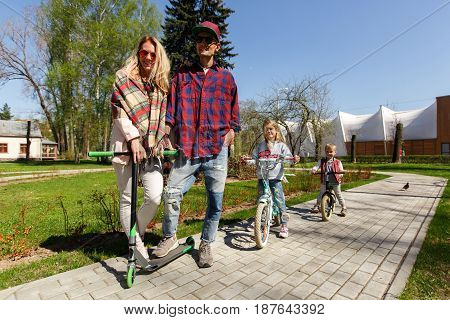 Young couple with children on scooters in park during day
